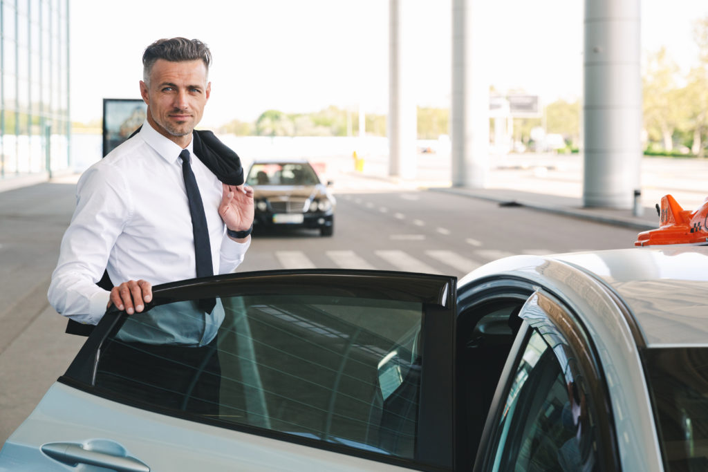 smiling-mature-businessman-getting-in-taxi-MQKY4WU-1024x683